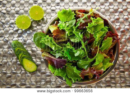 Green salad Mediterranean green and red lettucce spinach and cucumber on modern stainless steel
