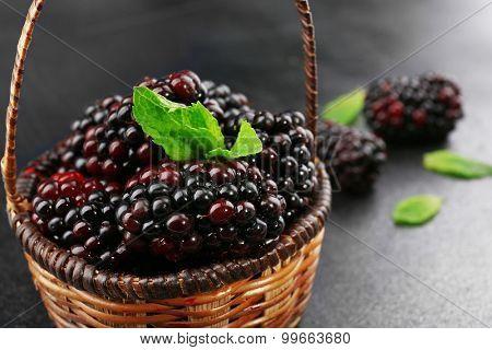 Ripe blackberries with green leaves in wicker basket on dark surface, closeup