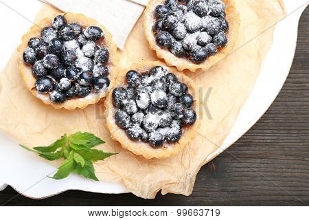 Delicious crispy tarts with black currants on parchment on wooden board, top view