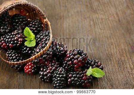 Ripe blackberries with green leaves in wicker basket on wooden background