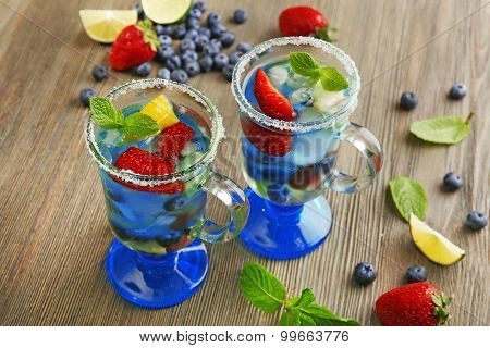 Glasses of berries juice on wooden background