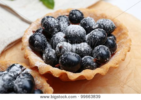 Delicious crispy tart with black currants on parchment, closeup