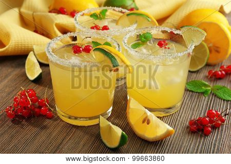Glasses of lemon juice with red currants on wooden table, closeup