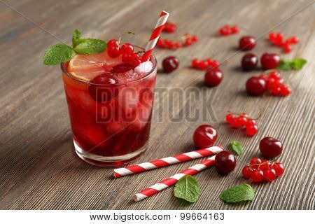 Glass of berry juice on wooden table, closeup