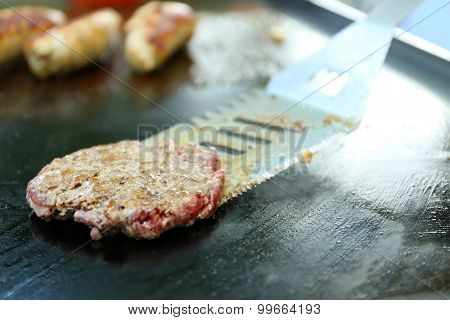 Burgers cooking in frying pan close up