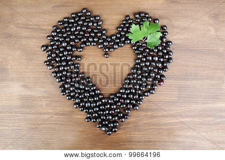 Black Currant in shape of heart on wooden background