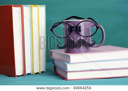 Books and cup with mustache on colorful background