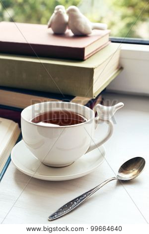Cup of tea with stack of books on windowsill, closeup