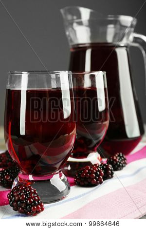Glasses of blackberry juice on wooden table, closeup