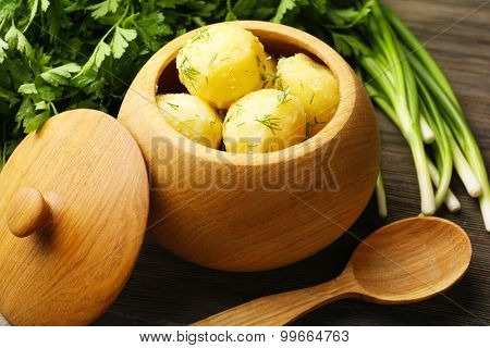 Boiled potatoes with dill in pot on table close up