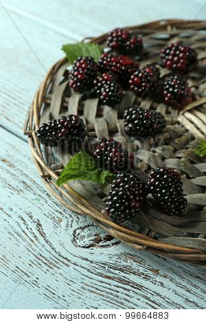 Heap of sweet blackberries with mint on table close up