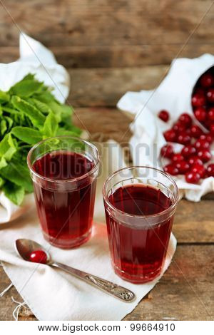 Two glasses with cherry juice on table, on wooden background