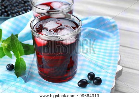 Glasses of fresh blackcurrant juice with ice cubes on checkered napkin on wooden table, closeup
