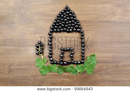 Black Currant in shape of house on wooden background