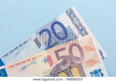 Seventy euro in various notes on light blue background