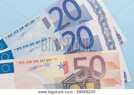 Ninety euro in various notes on light blue background