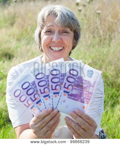 Old age woman holding 2500 euro