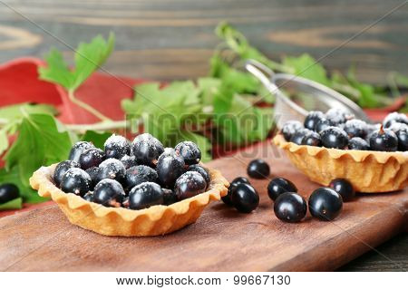 Delicious crispy tarts with black currants on wooden cutting board, closeup