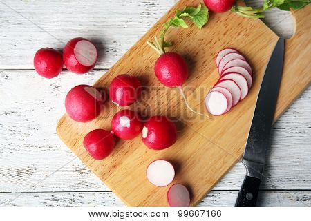 Fresh sliced radishes on cutting board close up