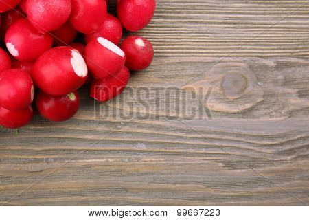 Heap of fresh radishes on wooden table close up background