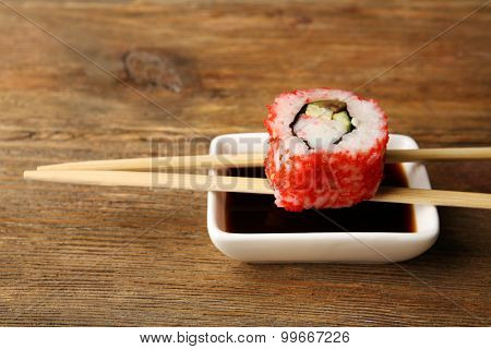Roll with sauce and sticks on wooden table close up