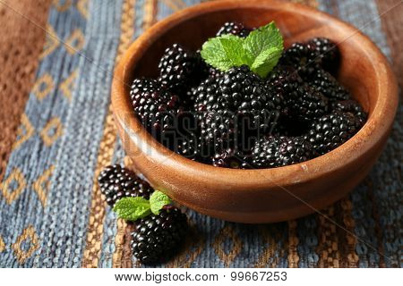 Ripe blackberry in bowl on color wooden background