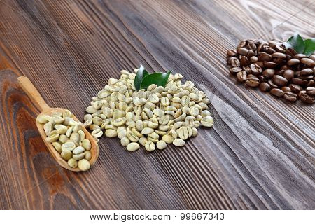 Green and brown coffee beans with spoon on wooden table close up