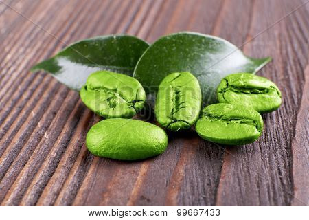 Coffee beans with leaves on wooden background