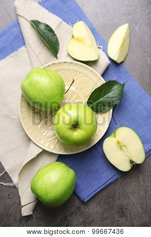 Green apples on wooden table with napkins, top view