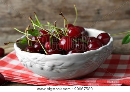 Cherries in bowl, on wooden background