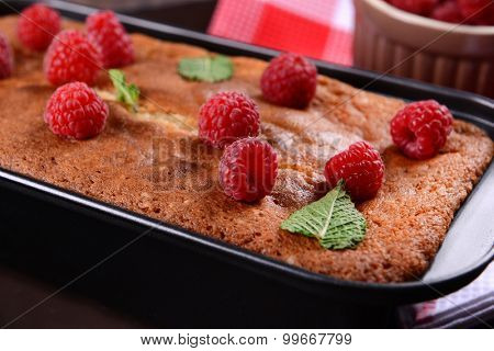 Fresh pie with raspberry in pan on wooden table, closeup