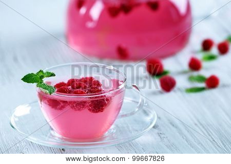 Cup and teapot of raspberry drink with berries on wooden table close up