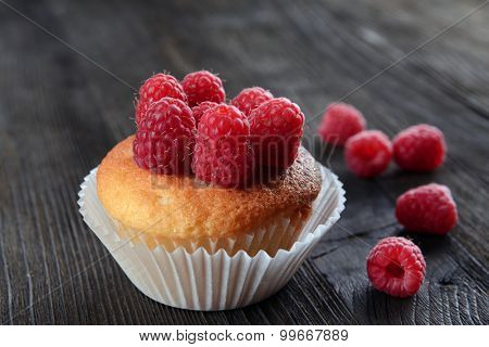 Delicious cupcake with berries on wooden table close up