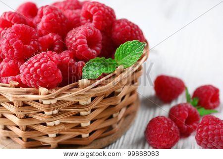 Fresh red raspberries in wicker basket on wooden table, closeup