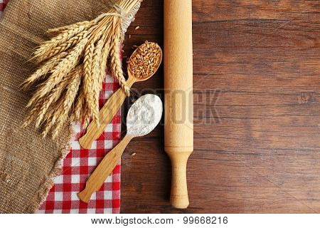 Flour and wheat on wooden table, top view
