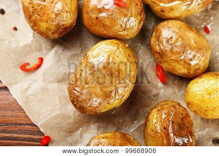 Baked spicy potatoes on parchment on wooden table, closeup