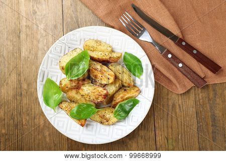 Baked potatoes with basil leaves in white plate on wooden table, top view