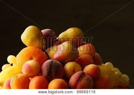 Heap of fresh fruits on dark background
