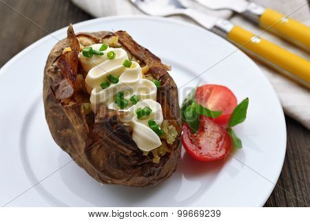 Baked potato mayonnaise and chives in white plate on wooden table, closeup