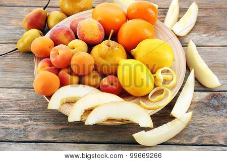 Heap of fresh fruits on wooden table close up