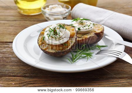 Baked potato mayonnaise and herbs in white plate on wooden table, closeup