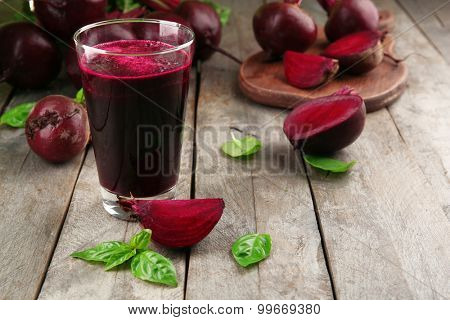 Glass of beet juice on wooden table, closeup