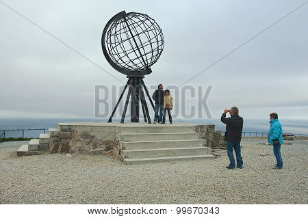 People make travel photo with symbolic globe at North Cape, Norway.