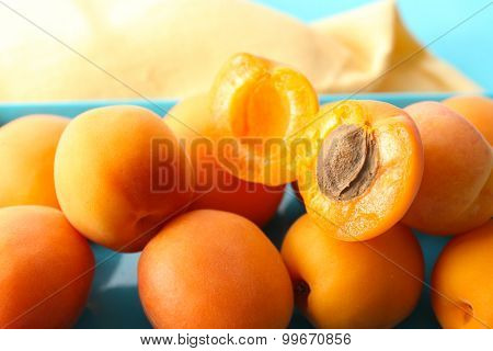 Ripe apricots on metal tray on table close up