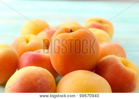 Heap of ripe apricots on wooden table close up