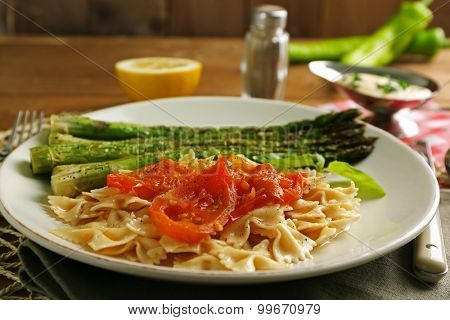 Roasted asparagus and tasty pasta with vegetables on plate on wooden table background