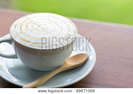 A Cup Of Coffee On Wooden Table And Green Grass Background.
