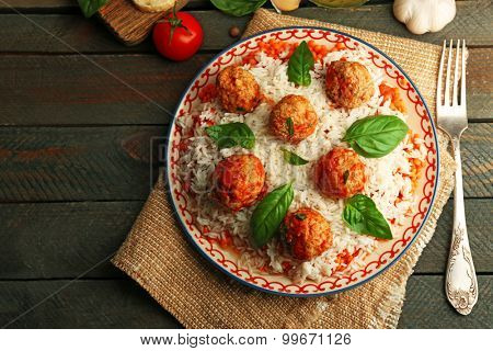 Meat balls in tomato sauce with boiled rice and lentil, wooden spoon on wooden background