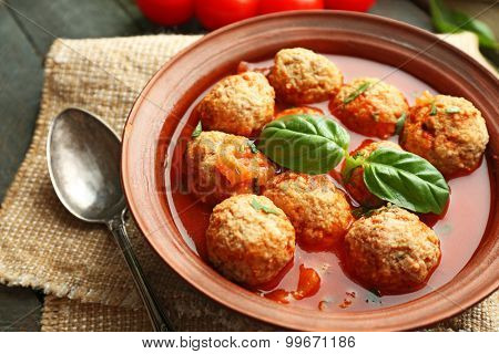 Meat balls with tomato sauce, wooden spoon on wooden background