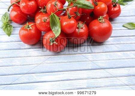 Fresh cherry tomatoes with basil on wooden table close up